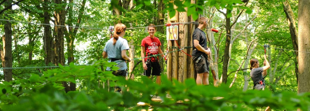 Group of young adults stand on a treetop platform watching a friend zip line across to another tree at Go Ape Treetop Adventure